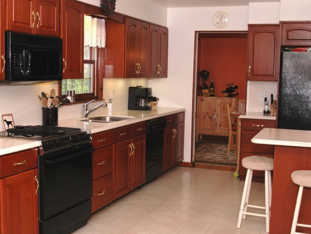 Cherry Wood Kitchen Cabinets With Black Appliances