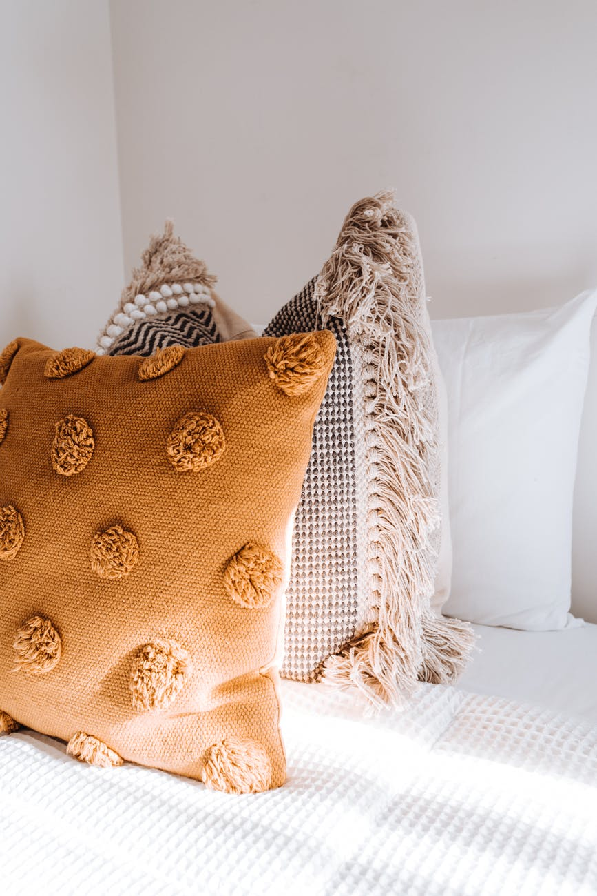 cozy pillows placed on bed