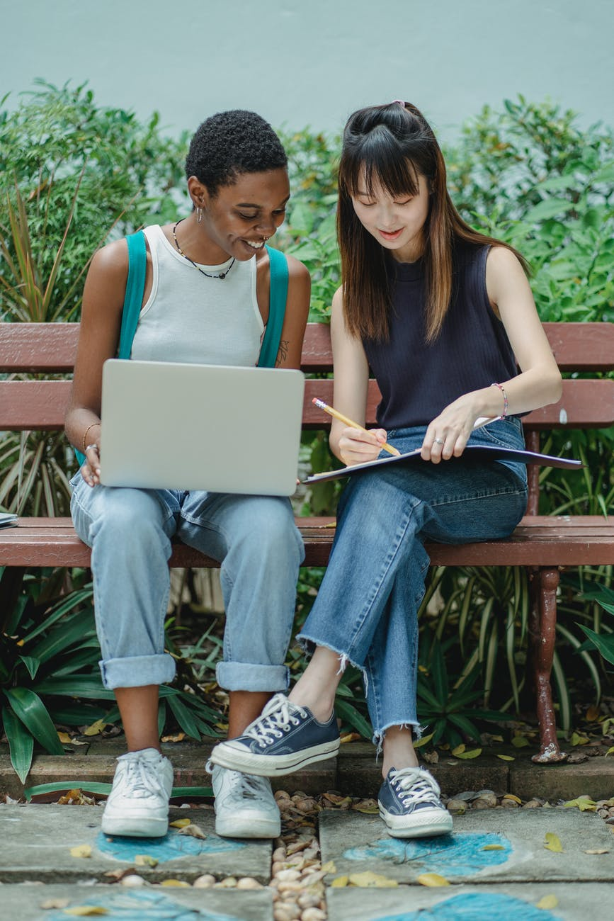 positive diverse female students preparing for exam together in park