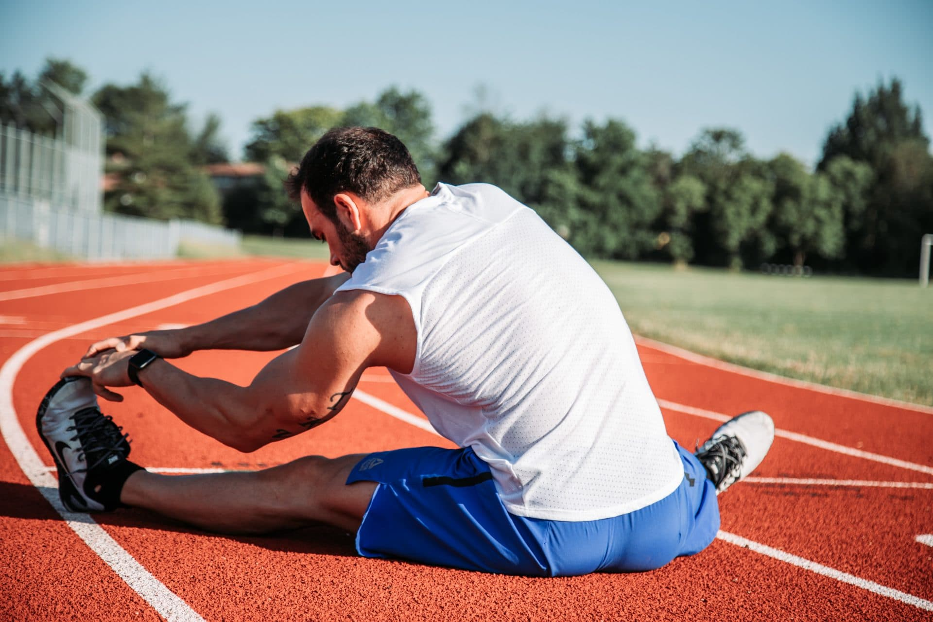 athlete stretching on running track