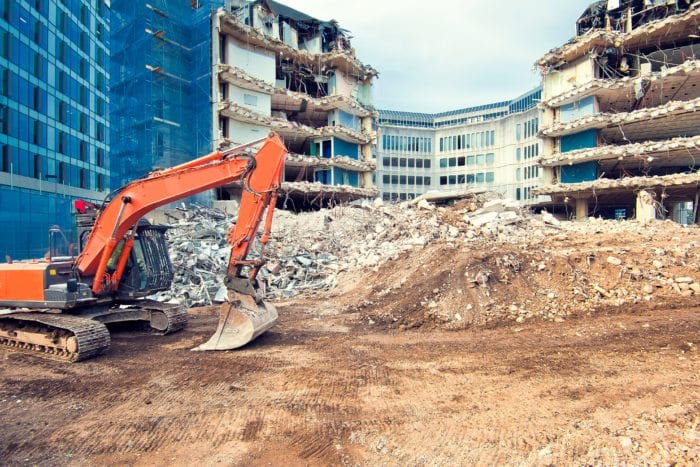 a crane is demolishing buildings