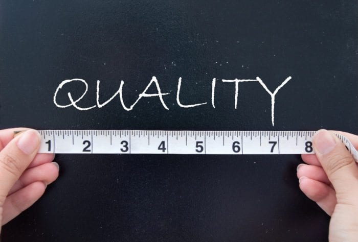 a man with a ruler and the word quality