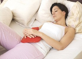 Woman with hot water bottle over her abdomen for menstrual discomfort.