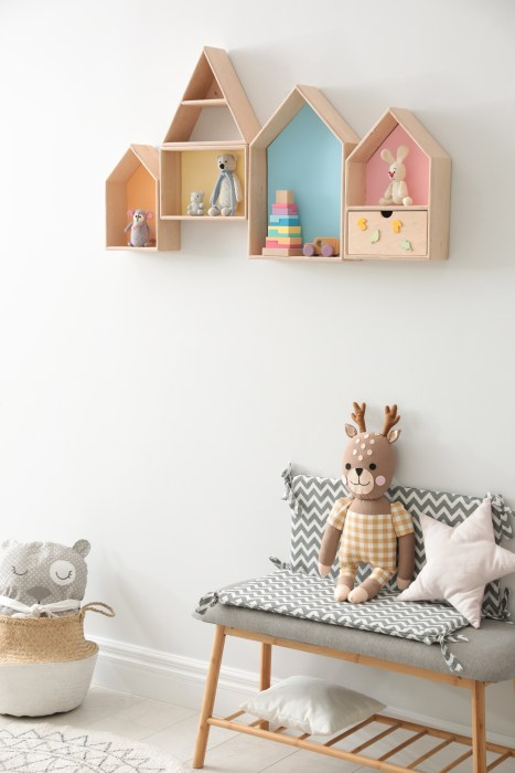 House shaped shelves and bench with toys in children's room. Interior design