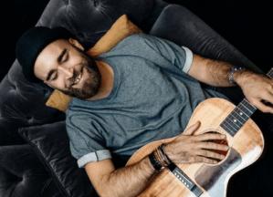Caruso, guitare en mains et sourire aux lèvres