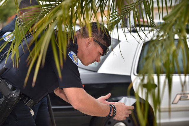 GARDEN GROVE PD Officer Steve Ortiz takes evidence photos using a camera built-in to the same tablet he uses to write a police report in the field. Photo by Steven Georges/Behind the Badge OC