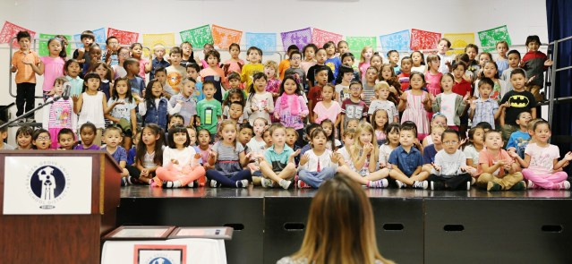KINDERGARTEN students at the Dual Language Immersion Academy at Monroe Elementary School welcomed public officials, community leaders and parents to their school with a song.