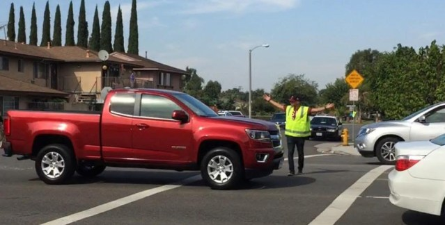 MOTORIST drives right by a police cadet in a crosswalk during an enforcement operation in Garden Grove (GGPD photo).