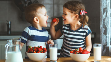 Two Kids Eating Fruit