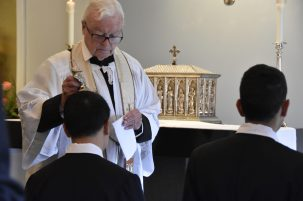 Fr Robinson blesses Br John Henry with the relic of St Philip
