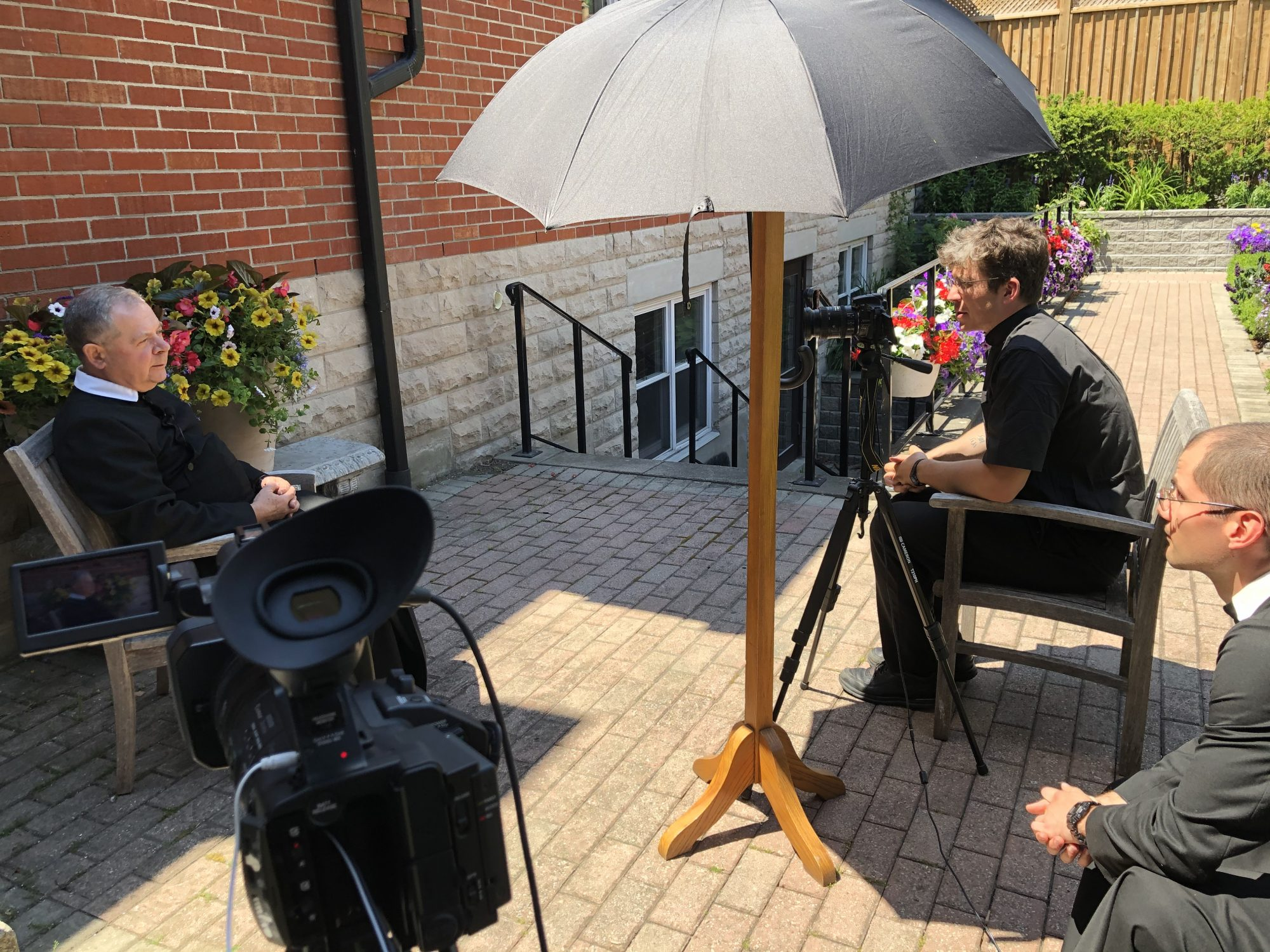Br Ted is interviewed by Br Carter and Br Bruno in the garden. Filming equipment is visible.