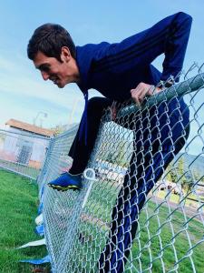 Landon scrambling over the fence.