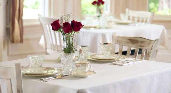 White covered dining tables set with white china and red roses.