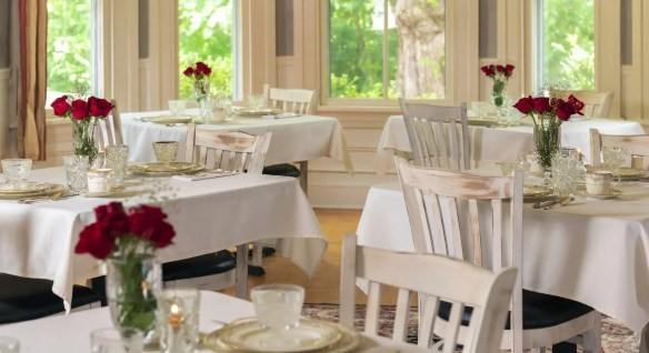 White airy dining room with tables set with white china and red roses