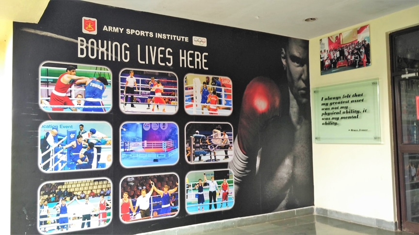 A wall mural made of a vinyl banner and pasted on the wall outside a boxing club. The wall sticker shows images of all the club's boxing champions in action.