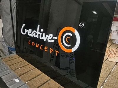 This image shows a lit acrylic shop board created for the web design and graphic institute, Creative Concepts.