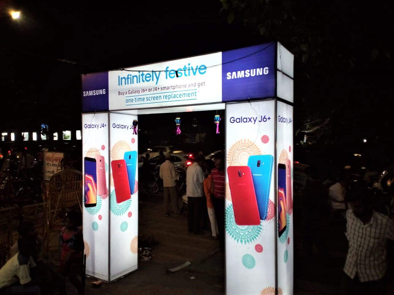 a brightly lit backlit promotional arch displaying ads for samsung mobiles installed in a crowded market place