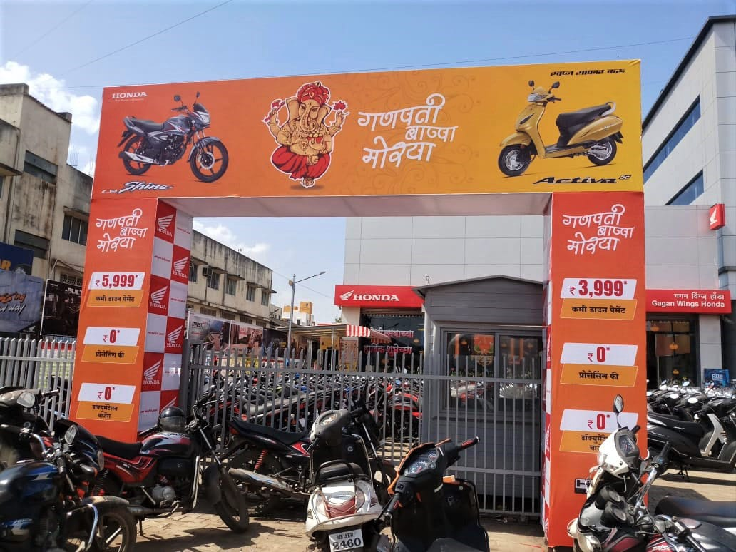 a huge printed arch gate for a ganpati mandal showing advertisements for Hero Honda motorcycles
