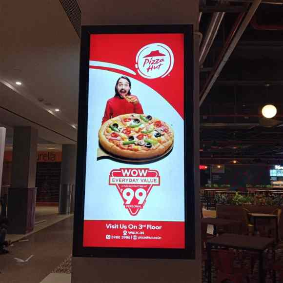night view of a glowing backlit board fixed on a pillar showing advertisement for pizza hut