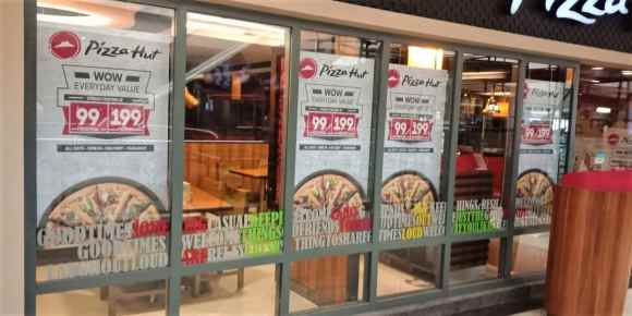 reverse glass sticker printing where the film carrying images of pizzas is pasted from inside the glass partitions at a Pizza Hut outlet