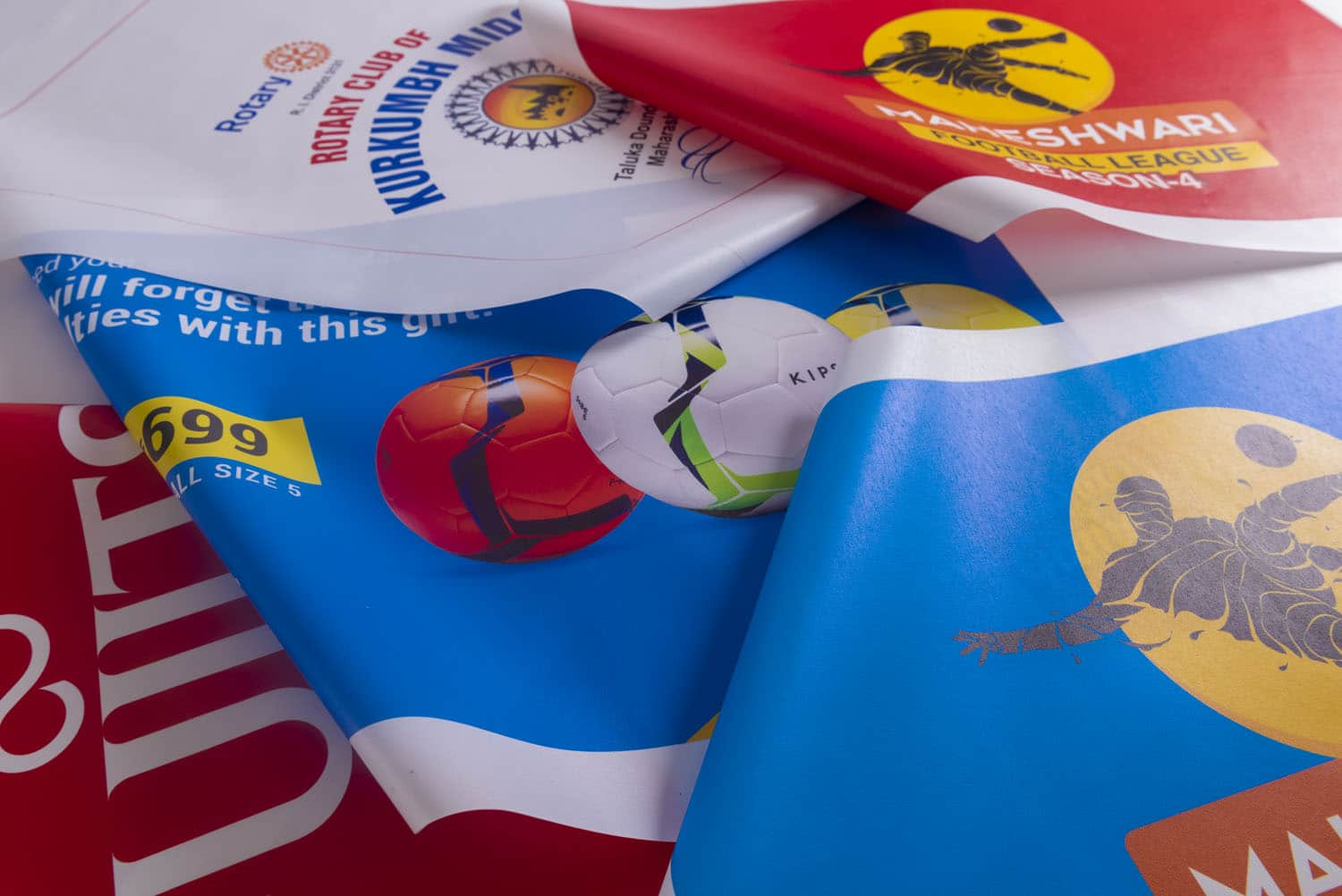 colourful flags and banners printed on cloth material spread out on a flat surface