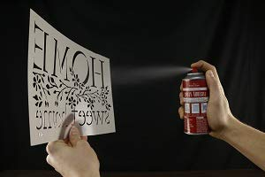 stencil adhesive spray being applied to a polyester laser cut stencil to hold the same in place while painting over it