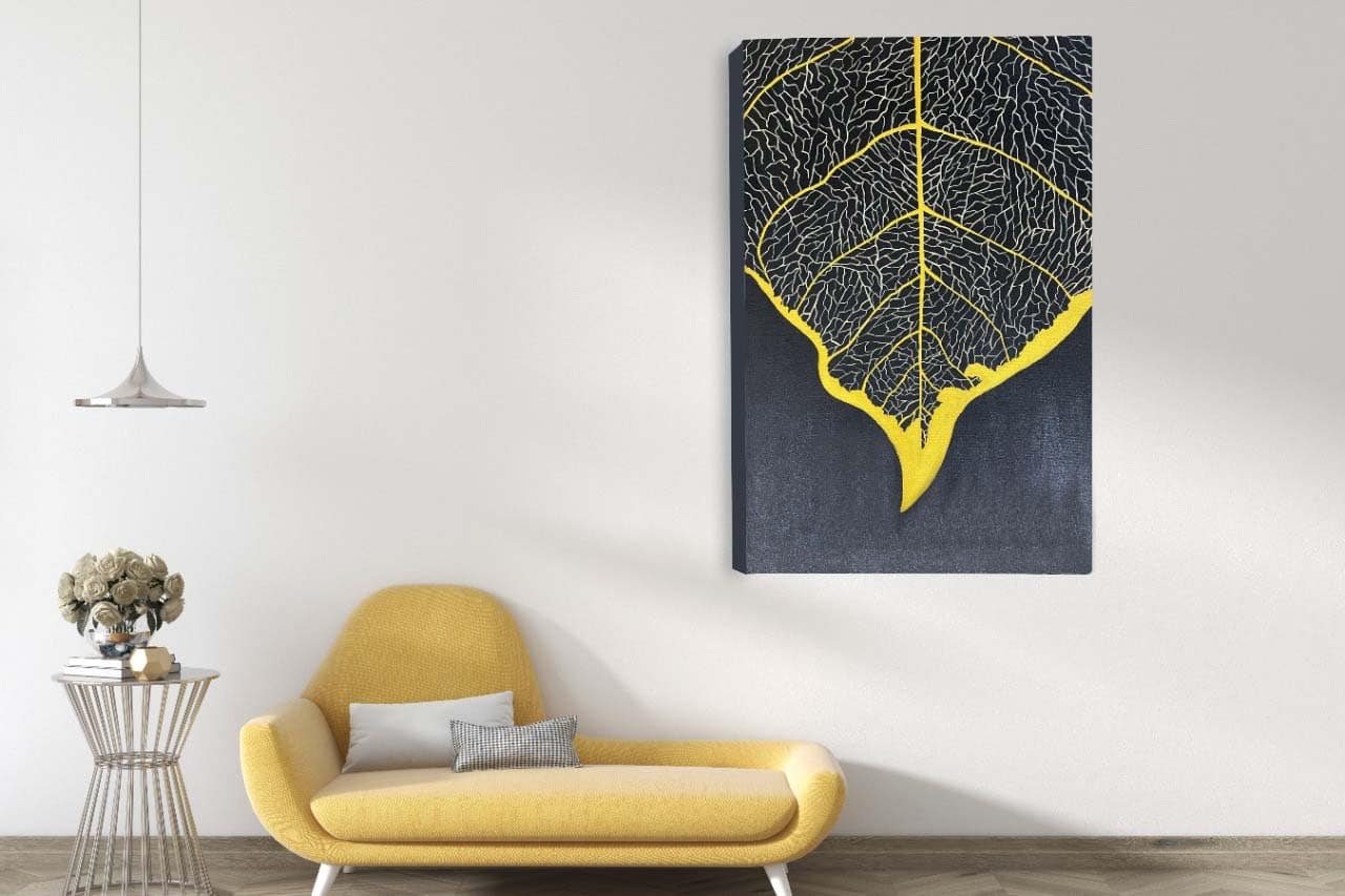 A large canvas painting showing the veins of a leaf chased in gold. This painting is placed on the wall in a living room next to a sofa.