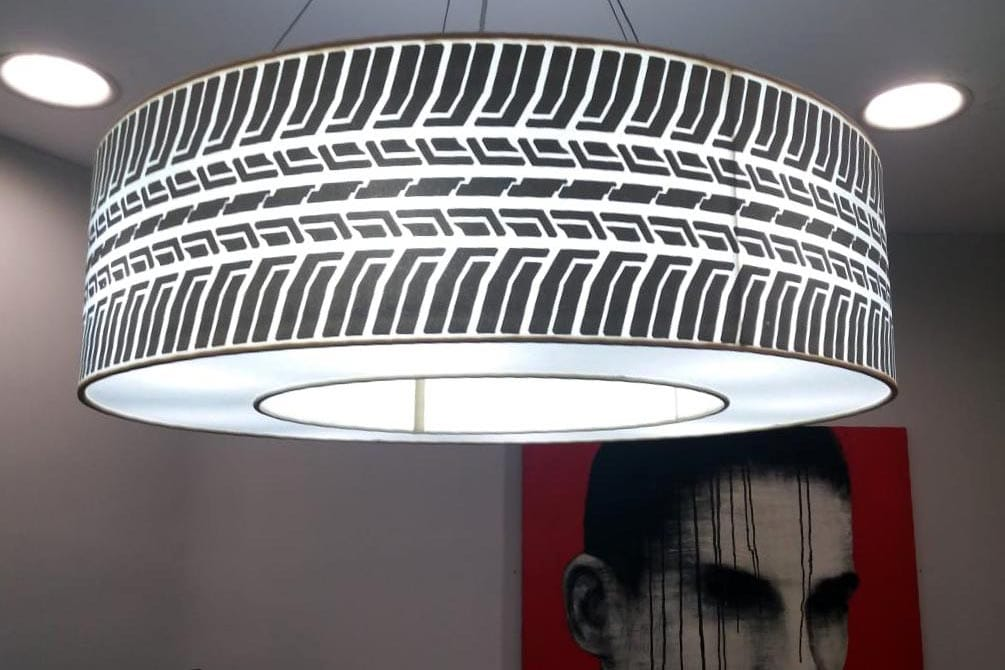 A brightly lit lampshade suspended from the ceiling showing a tyre threads pattern. This design is printed on the fabric stretched on the outside frame of the lamp. There is another framed canvas print on the wall behind it.