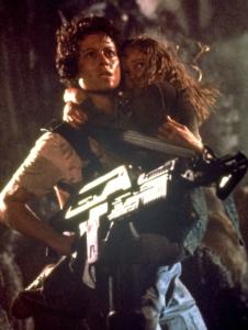 Alfakvinden Ripley med våben i den ene arm og Newt i den anden.