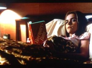 Sally Draper (Kiernan Shipka) læser Irv Levins bogoplæg, mens Don Draper og flere andre ser filmatiseringen i 6. sæson af Mad Men.