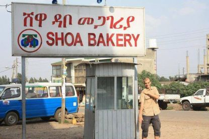 Quenelle hälsning framför skylt med reklam för ett bageri. Shoa syftar på Förintelsen