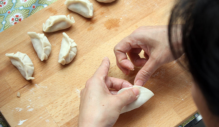 Make one pleat of the dumpling skin (only on one side, leaving the other side unpleated)