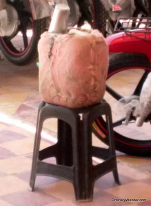 A fairly standard water jug wrapped in burlap to keep it cool. Atop sits the communal cup.