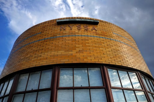 The curved prow shows the ceramic two-tone brick work with. The simple sign. Image source: DoCoMoMo.