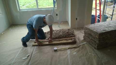 Students put under-floor insulation into the crawlspace