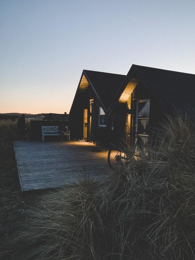Sunset glow over Danish Summerhouse in dunes near Hauvig Strand Beach
