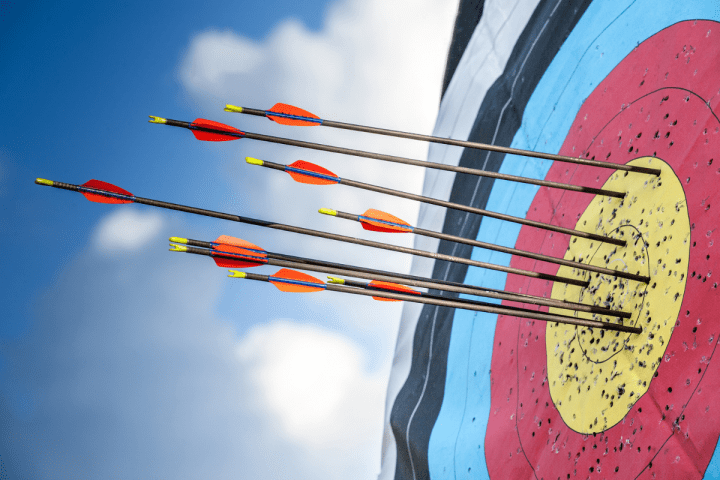 Oregon Senior Games - Archery - via Canva - A target with several arrows in the bullseye