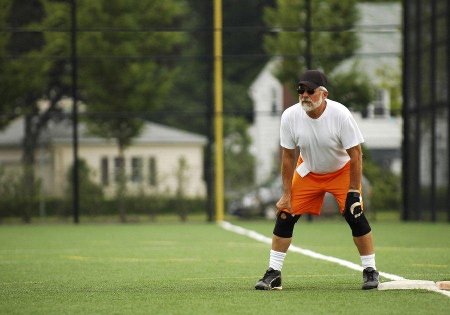 Senior Man On First Base, Poised To Run - Shutterstock - Glenda