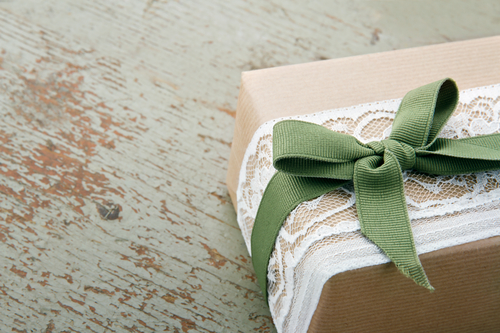 Decorative gift box wrapped in brown eco paper, white lace and green bow on wooden vintage background with copy space
