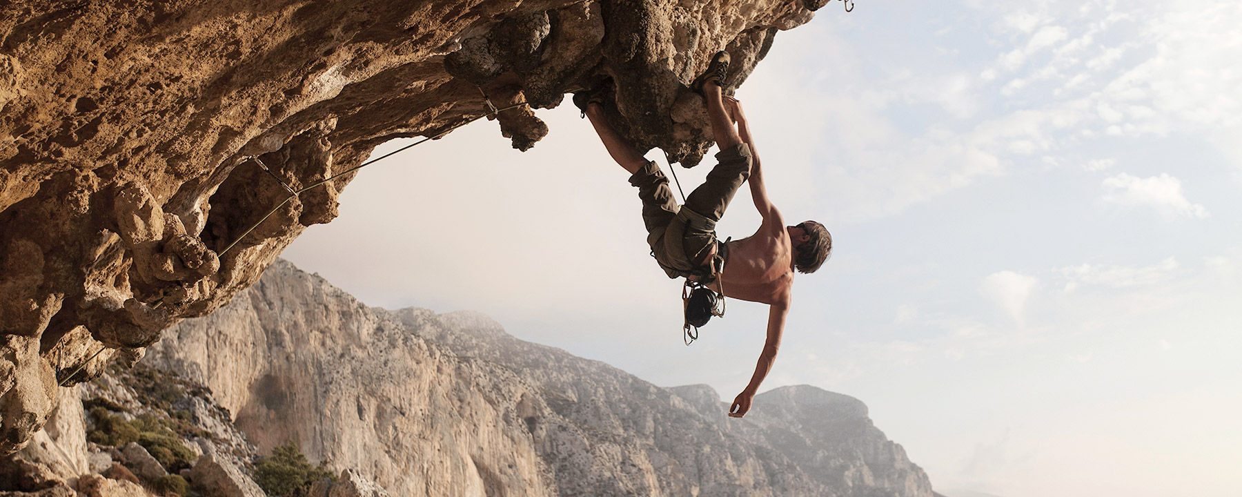 man challenging his limit by climbing rocks.