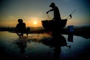 Two men fish very early in the morning on the ...
