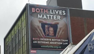 a billboard in Wellington CBD on a building. It includes a picture of a pregnant person holding a scan with the text: BOTH LIVES MATTER: BOTH DESERVE BETTER THAN AN EXTREME ABORTION LAW with the url voice forlife.org.nz