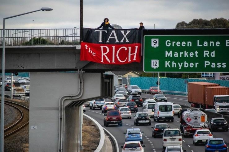 "Tasteful banner on the Auckland motorway bridge reads ""Tax the rich."""