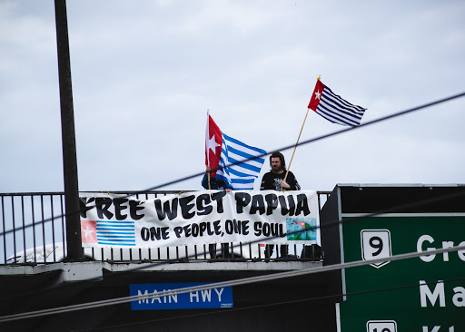 """OA members on the Auckland motorway overbridge drop a banner that reads """"Free West Papua: One people, one soul"""" and wave Morning Star flags."""