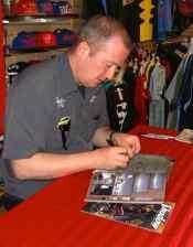 Serieförfattaren Garth Ennis sitter vid ett bord och signerar en utgåva av Preacher.