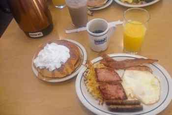 Del av frukostbord. Kaffe, apelsinjuice, pannkakor och en tallrik med korv, ägg, bacon, skinka och råraka.