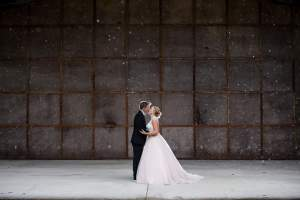 A gorgeous couple on their wedding day kiss on stage.