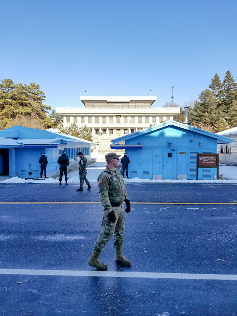 American soldier at the JSA on the border of South Korea and North Korea, with the iconic blue conference buildings in the background.