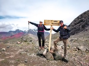 Two people celebrate at the top of Palomani Pass at 5200 meters in Peru