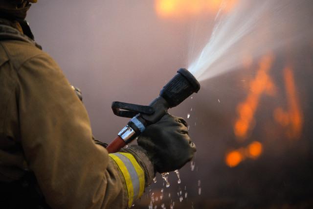 Spraying Fire Hose --- Image by © Robert Llewellyn/Corbis